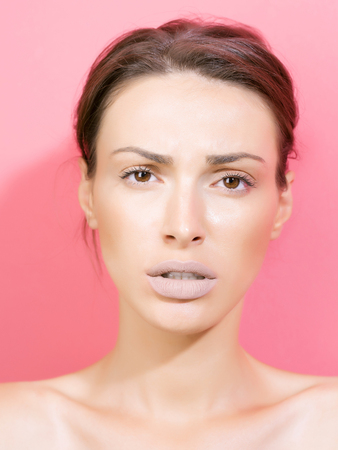 sorrowful: Young woman brunette with pretty sorrowful sexi face fashion makeup healthy perfect skin on pink background studio closeup