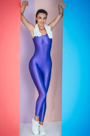 sexi: young pretty cute sexy woman or girl with slim fit body in sporty overall or jumpsuit violet color with white towel posing on red and blue colorful studio background
