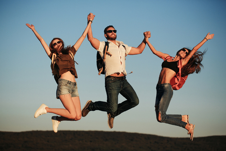 sexi: Bearded handsome man and two pretty sexy cute girls or women in jeans and shorts with backpacks outdoor on sunny day jumping on blue sky background Stock Photo