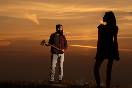 axe girl: Strong man lumberjack hipster with long beard and moustache in checkered shirt with axe in hand and silhouette of sexy cute woman or girl on twilight on natural sunset background