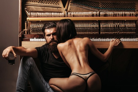man ass: handsome bearded man with long beard on serious face near young woman or girl with sexy body legs and buttocks has bare back in lingerie near old wooden piano keyboard