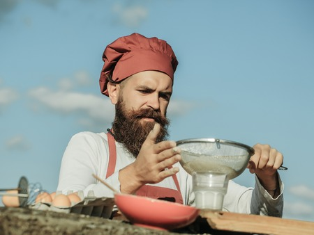 bolter: Man chef cook hipster with handsome bearded face in hat and white and red uniform bolting flour with sieve on blue sky background outdoor