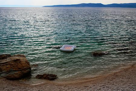 Leeg opblaasbaar matrass van het luchtbed op blauwe overzeese transparante ondiepe waterspiegel bij steenachtige strandkust en bergen op horizon Stockfoto