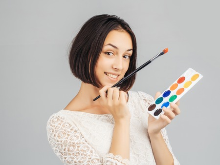 pretty sexy cute woman or girl with short brunette hair in white tracery blouse with colorful paint and long paintbrush smiling on gray studio background
