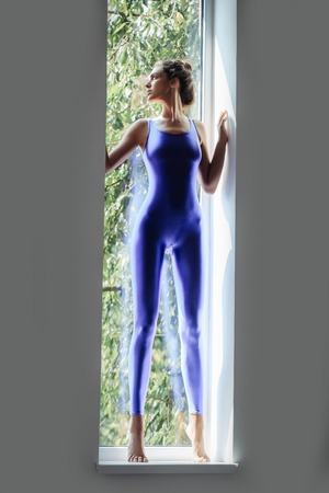 turnanzug: Young woman gymnast with prety face sexy slim body silhouette in blue leotard standing near window indoor
