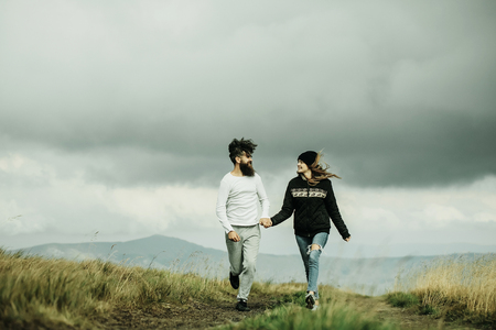 hoody: Couple of handsome bearded man in white shirt and pretty young cute girl or woman in black hoody holding hands and walking on meadow road on cloudy sky background