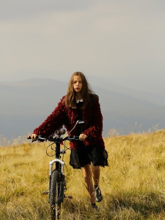Pretty sexy cute young woman or girl with long blonde hair and stylish look in red jacket walking with bike on mountain top with grass outdoor 스톡 콘텐츠
