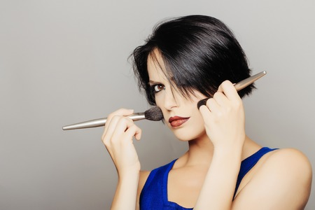 Girl with short dark hair red lips, blue dress and make up with face brushes applies blush on her cheeks in front of grey background