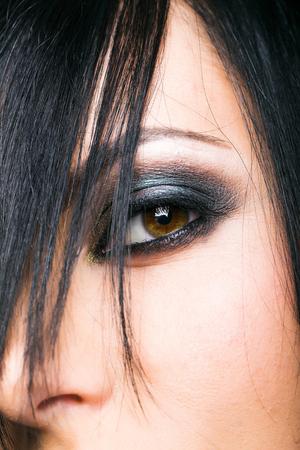 smoky black: Smoky eye make up with dark shadows and black mascara of pretty young girl with dark short hair Stock Photo