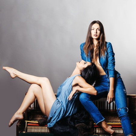 Two sexy young attractive girls with dark hair in blue clothes sit on the piano