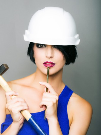 Attractive girl with short dark hair red lips and blue dress in white hard hat with hummer and nail in front of grey background