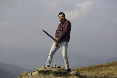 bearded man hipster with long beard and moustache in checkered shirt with axe in hand standing and smiling on stone on mountain top on sunny day
