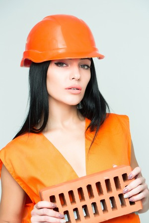 brick mason: pretty sexy cute builder woman or mason girl with long straight hair in orange overall uniform holds in hands brick with metal helmet isolated on white background Stock Photo