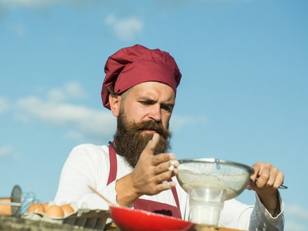 Man chef cook hipster with handsome bearded face in hat and white and red uniform bolting flour with sieve on blue sky background outdoor