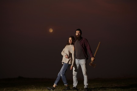 axe girl: Young couple of pretty girl and bearded man hipster with beard and axe on mountain top at night on moon light