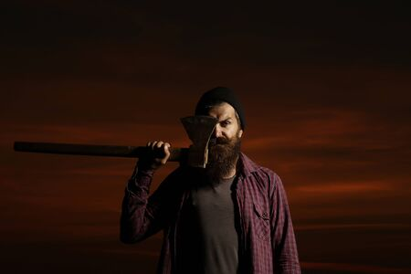 muscularity: Strong man lumberjack hipster with long beard and moustache in checkered shirt with axe in hand on twilight on darkness background