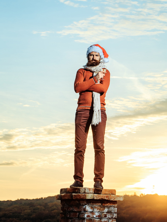 stylish men: young bearded santa claus man with long beard in red sweater pants and new year hat in scarf with glass of champagne drinking and celebrating christmas or xmas on sunny blue sky on brick chimney