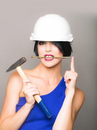 Attractive girl with dark short hair red lips blue dress in white hard hat with hummer and nail in mouth on grey background