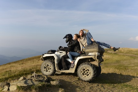 Handsome man and two pretty girls ride quad bike on field road on mountain scene