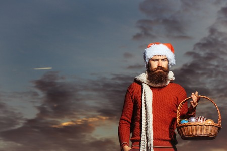 stylish men: young handsome bearded santa claus man with long beard in red sweater and new year hat in scarf holds basket with decorative christmas or xmas balls on sunny blue sky in twilight, copy space