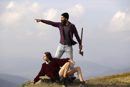 Bearded man hipster with beard and moustache with axe and pretty girl young sexy woman on mountain top on foggy sky