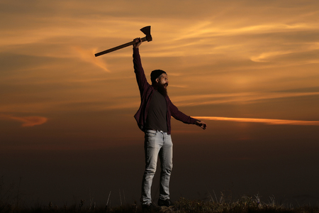 hatchet man: Bearded man hipster with beard and moustache in hat stands with axe on mountain top on sunset sky