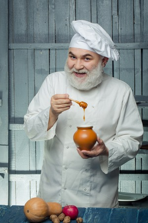 Bearded man cook in chef hat with apple nuts pumpkin and honey on wooden background Zdjęcie Seryjne