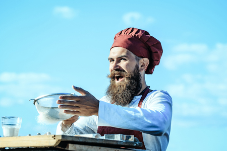 Man chef cook hipster with handsome bearded expressive laughing face in hat and white and red uniform bolting flour with sieve on blue sky background outdoor Stockfoto
