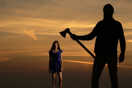axe girl: Dark silhouette of man with axe and pretty girl young beautiful woman stand on mountain top on sunset sky
