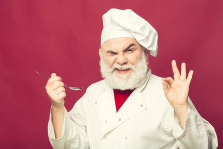 Bearded man cook in chef hat with spoon closeup in studio on pink background 版權商用圖片