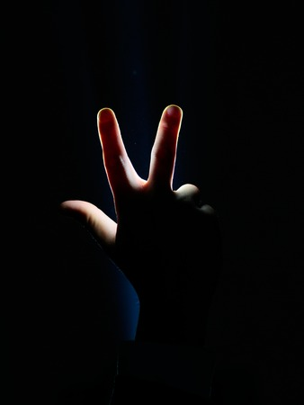 dark silhouette of human male hand with raised fingers in spotlight or backlight light with gesture on black background with dramatic projector shine ray or beam