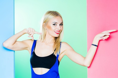 Pretty cute girl or beautiful blond woman in sexy dress with red lips and long hair in studio on colorful blue pink and green background, copy space