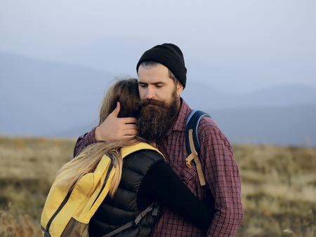 Romantic couple of woman or girl and handsome bearded man embrace on cliff over mountain tops outdoor with yellow backpack