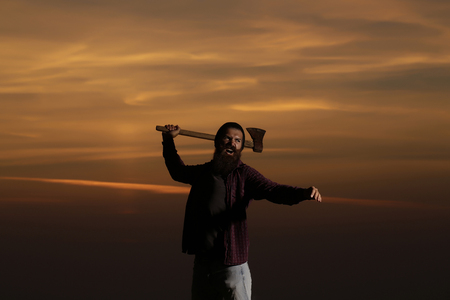 Strong man lumberjack hipster with long beard and moustache in checkered shirt with axe in hand on twilight on natural sunset background
