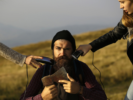 handsome bearded man with mustache and long lush beard on face sit with axe and two female hands shave him on mountain top on blurred background