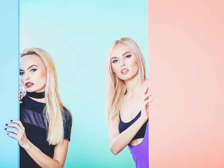 Pretty cute girls or beautiful blond women twins in sexy dress with red lips and long hair in studio on colorful orange blue and green background, copy space