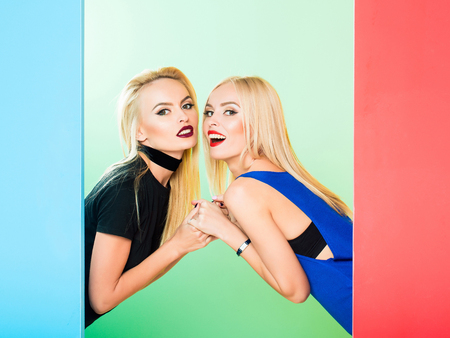 Pretty cute girls or beautiful blond women twins in sexy dress with red lips and long hair in studio on colorful blue and green background, copy space Stock Photo