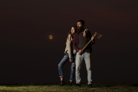 embracing couple of strong man lumberjack hipster with long beard and moustache in checkered shirt with axe in hand and sexy woman or cute girl on twilight on natural sunset background