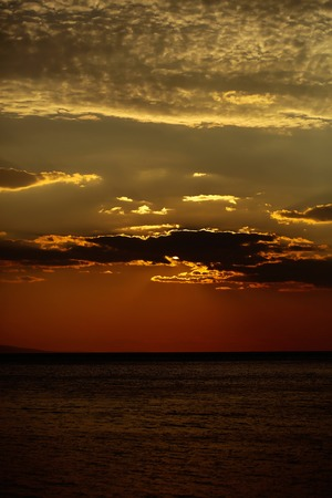 Spectacular dramatic dark sky at sunset with clouds over sea or ocean water horizon on evening seascape on natural background Banco de Imagens