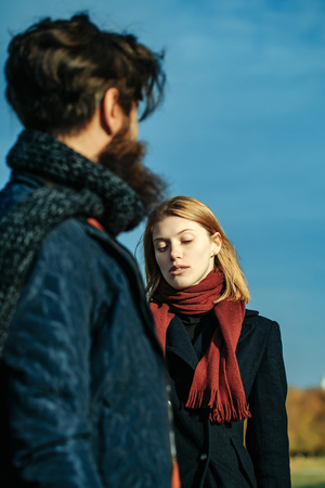conversaciones: Pretty girl young beautiful woman with red hair and scarf talks to bearded man hipster outdoors in park on autumn day on blue sky Foto de archivo