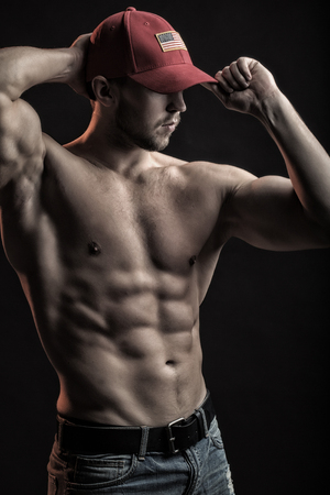 One sexual strong young man with muscular body in red sport  cap standing posing in studio on black background, vertical picture