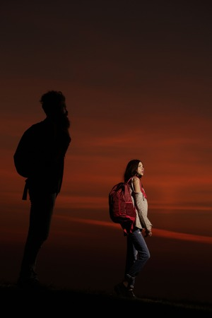 silhouette of strong man hipster with long beard and sexy cute woman or girl with backpack on twilight on darkness background