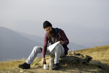 handsome bearded man with mustache long lush beard in checkered shirt black hat sit on stone and reading map on mountain top on sunny day Stok Fotoğraf