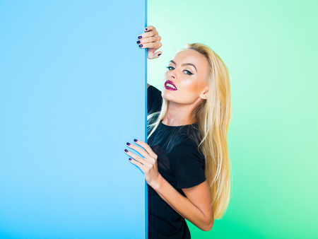Pretty cute girl or beautiful blond woman in sexy dress with red lips and long hair in studio on colorful blue and green background, copy space