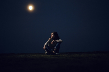 sits: Pretty girl beautiful young woman sits on mountain top at night on moon light