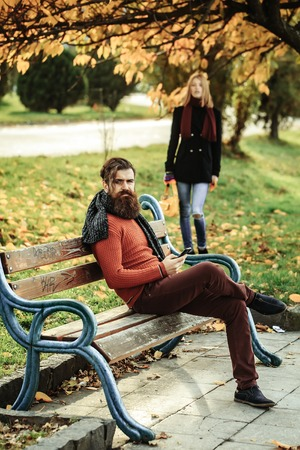 Young couple of pretty cute sexy girl or woman and bearded man hipster sits on bench outdoors in autumn park with yellow leaves and green grass on natural background
