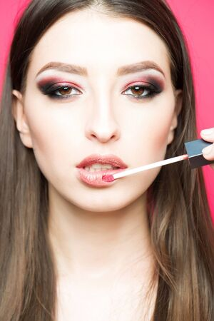 beige lips: Pretty sexy cute woman or girl with long brunette hair and smooth skin has fashion makeup and beige lipstick brush in mouth or lips on pink background, close up Stock Photo