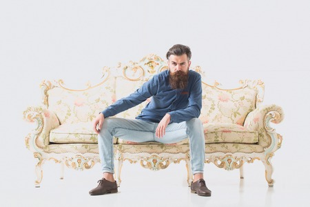 Handsome bearded young man in blue shirt and jeans sits on luxurious couch with flower pattern isolated on white background