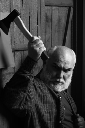 Senior man. Old man with white beard holding axe on paper in wooden wall, black and white