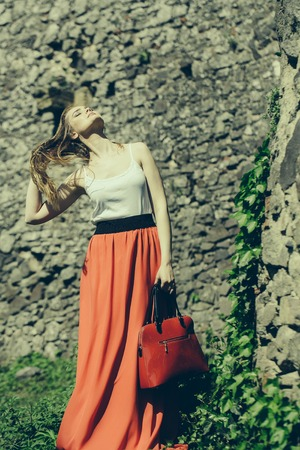 pretty young sexy woman or girl with cute face and long hair in fashionable red skirt with bag sunny outdoor with green leaves on stony wall background